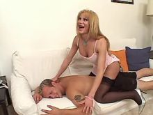Hot blonde shemale in stockings sucks cock on sofa